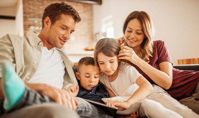 A Family sitting on the couching looking at an ipad